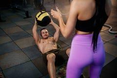 Geschikte Kaukasische mens die buikbaloefening met persoonlijke trainer in de gymnastiek doen royalty-vrije stock fotografie