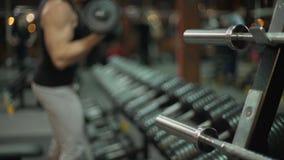 Geschikte kerel die alternatief lift-UPS met domoren in gymnastiek, gewichtheffen doen stock footage