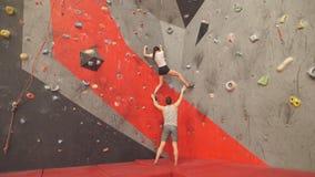 Geschikte man en vrouwen opleiding bij de het beklimmen zaal stock footage