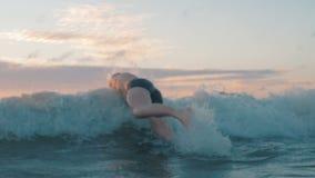 Geschikte mens die in oceaan in langzame motie springen stock videobeelden