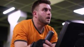 Geschikte mens die op hometrainer bij de gymnastiek uitwerken stock video