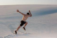 Geschikte mens die snel op het zand lopen Krachtige agent opleiding openlucht op de zomer stock foto