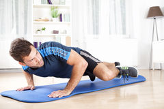 Geschikte Mens Planking op Mat While Lifting One Leg royalty-vrije stock afbeelding