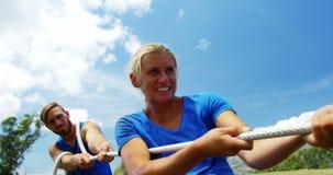 Geschikte mensen die touwtrekwedstrijd spelen tijdens hindernis trainingscursus 4k stock video