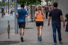 Geschikte millennial paarjogging op de stoep in stad de van de binnenstad van Toronto royalty-vrije stock foto's