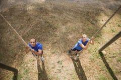 Geschikte persoon die onderaan de kabel tijdens hinderniscursus beklimmen Royalty-vrije Stock Foto