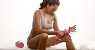Geschikte Spaanse vrouw die na het opheffen van gewichten rusten Stock Afbeeldingen