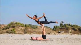 Geschikte sportieve paar het praktizeren acroyoga met partner samen op het zandige strand stock fotografie