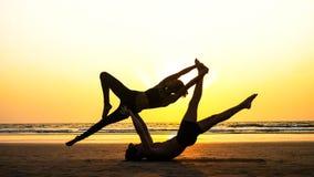 Geschikte sportieve paar het praktizeren acroyoga met partner samen op het zandige strand royalty-vrije stock afbeelding