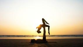 Geschikte sportieve paar het praktizeren acroyoga met partner samen op het zandige strand stock foto's