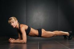 Geschikte sportieve vrouw die de oefening van de plankkern doen royalty-vrije stock fotografie
