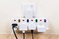 Geschikte veelvoudige elektriciteitsstoppen in bijlage aan multiadapter Stock Afbeelding