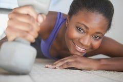 Geschikte vrouw die bij de domoor van de cameraholding glimlachen Royalty-vrije Stock Foto