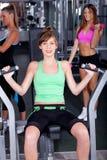 Geschikte vrouw die bij gymnastiek uitwerkt stock foto