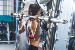 Geschikte vrouw die de oefening van de schouderpers met een machine van Smith van de gewichtsbar doen bij gymnastiek royalty-vrije stock foto