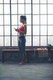 Geschikte vrouw die muziek op apparaat in zoldergymnastiek selecteren Royalty-vrije Stock Afbeelding