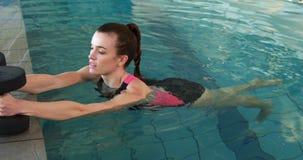 Geschikte vrouw die oefening met schuimdomoren doen in zwembad stock videobeelden