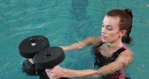 Geschikte vrouw die oefening met schuimdomoren doen in zwembad stock video