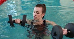 Geschikte vrouw die oefening met schuimdomoren doen in zwembad stock footage