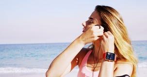 Geschikte vrouw die oortelefoons in haar oor zetten vóór jogging stock videobeelden