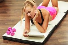 Geschikte vrouw die op vloer met tabletpc liggen Stock Afbeeldingen