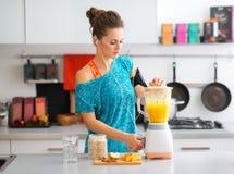 Geschikte vrouw die in trainingtoestel in keuken een smoothie maken royalty-vrije stock afbeeldingen