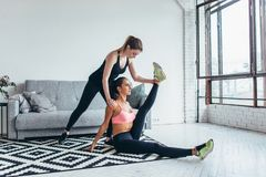 Geschikte vrouw die uitrekkende oefeningen met behulp van vriend doen die haar been thuis houden stock afbeeldingen