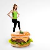 Geschikte vrouw die zich op een cheeseburger bevinden stock fotografie