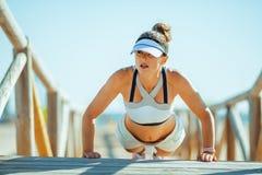 Geschikte vrouw jogger in geschiktheidskleren op zeekust die opdrukoefeningen doen royalty-vrije stock foto's