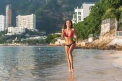 Geschikte vrouwelijke atleet die bikini dragen die op strand met zon die in camera en de heuvels van de hoteltoevlucht op achterg royalty-vrije stock afbeelding