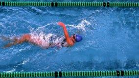 Geschikte vrouwelijke zwemmer die de achterslag in zwembad doen stock videobeelden