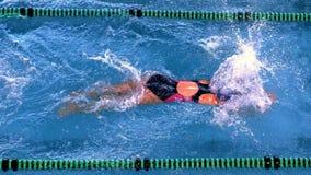 Geschikte vrouwelijke zwemmer die de vlinderslag in zwembad doen stock videobeelden