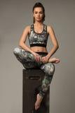 Geschikte vrouwen die sportkleren op de grijze achtergrond dragen stock afbeeldingen