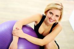 Geschikte vrouwenzitting op de vloer met fitball Stock Foto