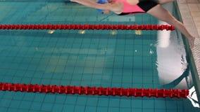 Geschikte vrouwenzwemmer die in pool duiken stock footage