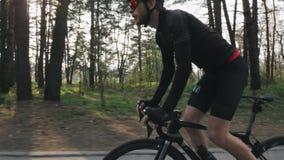 Geschikte zekere fietser op een fiets uit het zadel in het park Sterke beenspieren die pedalen spinnen Het cirkelen concept Langz stock videobeelden