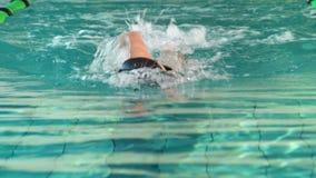 Geschikte zwemmer die de voorslag in het zwembad doen stock footage