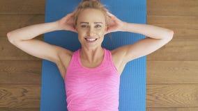 Geschiktheid bepaalde midden oude vrouw die thuis doend kraken op gymnastiekmat liggen stock videobeelden