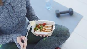 Geschiktheid en gezond voedsel De vrouw rust binnen en eet een gezond voedsel na een training in een wit stock videobeelden
