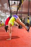 Geschiktheid TRX opleidingsoefeningen bij de gymnastiekvrouw en mens Stock Afbeelding