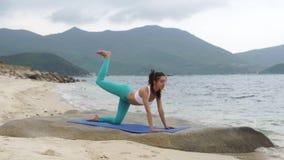 Geschiktheids gezonde vrouw die sportieve oefening op strand doen buiten bij zonsondergang stock video