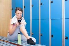 Geschiktheids glimlachende vrouw die slimme telefoon in kleedkamer met behulp van Royalty-vrije Stock Fotografie