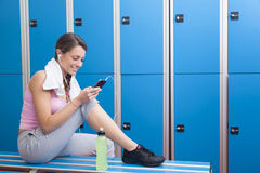 Geschiktheids glimlachende vrouw die slimme telefoon in kleedkamer met behulp van Stock Foto's