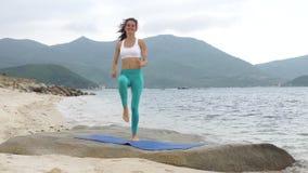 Geschiktheids glimlachende vrouw die sportieve oefening op strand doen buiten bij zonsondergang stock footage