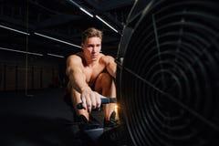 Geschiktheids jonge mens die het roeien machine in de gymnastiek met behulp van stock foto's