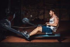 Geschiktheids jonge mens die het roeien machine in de gymnastiek met behulp van en het gillen royalty-vrije stock fotografie