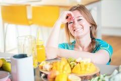 Geschiktheids jonge vrouw het drinken sinaasappel smoothie in Keuken stock foto's