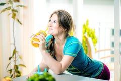 Geschiktheids jonge vrouw het drinken sinaasappel smoothie in Keuken royalty-vrije stock afbeelding