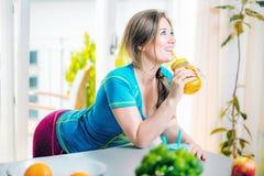 Geschiktheids jonge vrouw het drinken sinaasappel smoothie in Keuken royalty-vrije stock afbeeldingen
