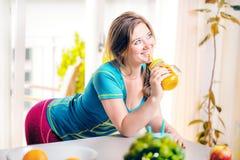 Geschiktheids jonge vrouw het drinken sinaasappel smoothie in Keuken royalty-vrije stock foto's